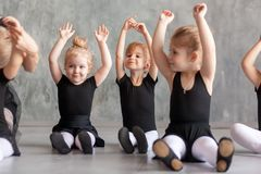 Little girls ballerines. Little girls ballerina in black dresses, belk tights and pointe shoes sit on the floor and hold hands over their head for warm-up before Royalty Free Stock Photography