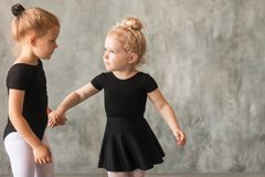 Little girls ballerines. Two small fair-haired girls ballerinas in black packs, white pantyhose, white pointe shoes learn to dance a Russian ballet in a black royalty free stock photography