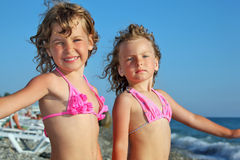 Little girls on beach, placed hands in sides Royalty Free Stock Photo