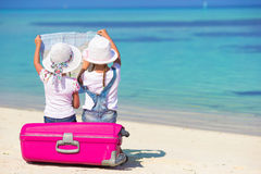 Little girls with big suitcase and map at tropical Royalty Free Stock Image