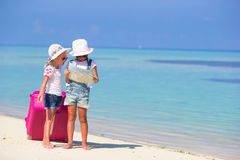Little girls with big suitcase and map at tropical Stock Photography