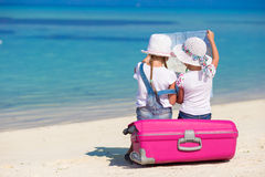 Little girls with big suitcase and map at tropical Royalty Free Stock Photo
