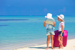 Little girls with big suitcase and map at tropical. Little adorable girls with big colorful suitcase in hands walking on tropical beach Stock Images