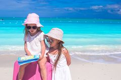 Little girls with big suitcase and map on tropical Royalty Free Stock Image