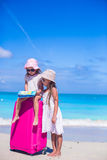 Little girls with big suitcase and map on tropical Stock Photos