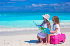 Little girls with big suitcase and map on tropical Stock Image