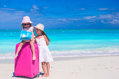 Little girls with big suitcase and map on tropical Royalty Free Stock Photography
