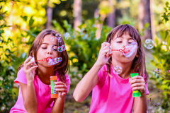 Little girls blowing bubbles with the wand in the park. Little girls are blowing bubbles with the wand in the park stock photography