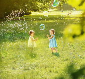 Little girls blowing soap bubbles on a summer meadow Stock Photo