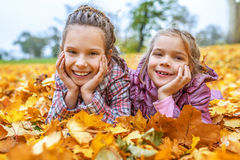 Little girls buried in autumn leaves yellow Royalty Free Stock Photo