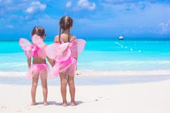 Little girls with butterfly wings on beach summer vacation. Adorable little girls with butterfly wings like butterfly on beach tropical vacation stock photo