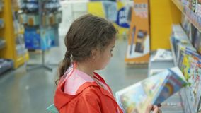 Little girls buy books in the supermarket stock video