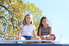 Little girls on a car Royalty Free Stock Photo
