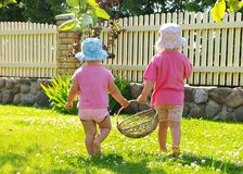 Little girls carrying basket Stock Image