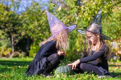 Little girls casting a spell on Halloween in witch Stock Images
