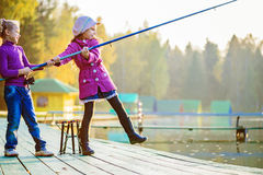 Little girls catches fishing rod Royalty Free Stock Photo
