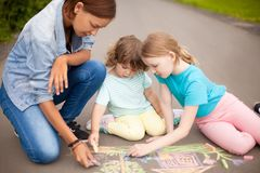 Babysitter or kindergarten concept. Children drawing with color. Little girls chalking at the asphalt with elder sister or nanny. Sisters friendship. Best royalty free stock photography