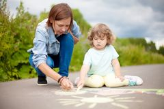 Babysitter or kindergarten concept. Children drawing with color chalk. Little girls chalking at the asphalt with elder sister or nanny. Sisters friendship. Best Royalty Free Stock Image