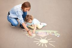 Babysitter or kindergarten concept. Children drawing with color. Little girls chalking at the asphalt with elder sister or nanny. Sisters friendship. Best royalty free stock photo