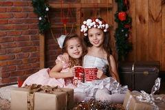 Little girls with Christmas knitted cups. Royalty Free Stock Image