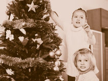 Little girls with Christmas tree Stock Photo