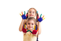 Little girls with colored hands. Two cute little girls in black and yellow shirts with ponytails and colored hands on white background in studio Royalty Free Stock Images
