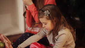 Little girls in comfortable home clothes sitting on floor in beautiful Christmas decorations. Two little sisters decorating Christmas tree with fir-cone. New stock video