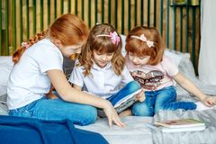 Little girls are considering a book. The concept of lifestyle, c stock photo