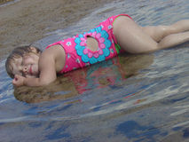 A Little Girls Contentment. Young girl loving the water on a hot Summer day stock photos