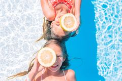 Little girls covering eyes with lemon halves near eyes on background swimming pool. Little girls covering eyes with citrus lemons posing isolated over swimming royalty free stock photography