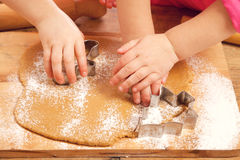 Little girls cutting gingerbread cookies Stock Images