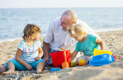 Little girls with dad playing at sea Royalty Free Stock Photography