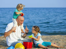 Little girls with dad  on  sea shore Royalty Free Stock Photography