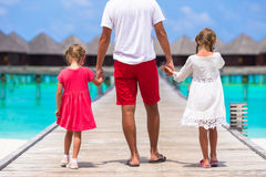 Little girls with dad on wooden jetty near water Royalty Free Stock Images