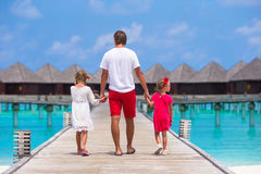 Little girls with dad on wooden jetty near water Royalty Free Stock Photo
