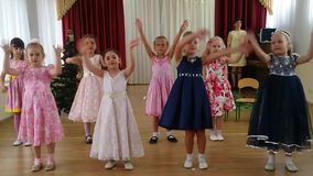 Little girls dance and sing the song. A morning performance in kindergarten stock video footage