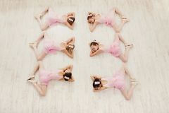 Little girls dancing ballet in studio. Young ballerinas stretching before performance, classical dance school, copy space, top view royalty free stock image