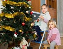 Little girls decorating Christmas tree Stock Image