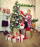Little girls decorating Christmas tree and preparing gifts Stock Photography