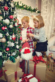 Little girls decorating Christmas tree and preparing gifts Stock Photo