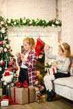 Little girls decorating Christmas tree and preparing gifts Royalty Free Stock Image