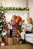 Little girls decorating Christmas tree and preparing gifts Stock Photos
