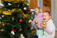 Little girls decorating Christmas tree Stock Photos