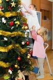 Little girls decorating Christmas tree Stock Photo