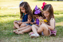 Little girls distracted by technology Stock Photography
