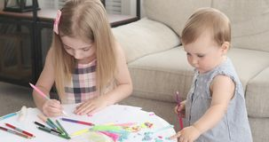 Little girls doing art and craft activity at home. Baby girl with her sister drawing with colored pencil at home stock video