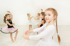 Little girls doing exercises in light ballet class. Portrait of adorable ballerina, six years old girl, standing in first position during ballet class stock photography