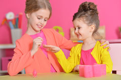 Little girls doing manicure. Cute little girls with stylish hairstyles doing manicure royalty free stock photos