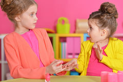 Little girls doing manicure. Cute little girls with stylish hairstyles doing manicure stock image