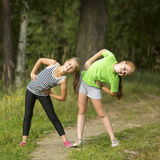 Little  girls doing morning exercises outdoors. Royalty Free Stock Photography